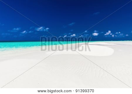 Small empty sandbar in the middle of tropical lagoon in atoll of Maldives