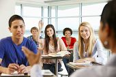 Multi racial teenage pupils in class one with hand up poster