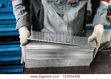 small stack of steel plates on the bench miller hand in working gloves