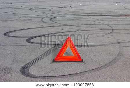 Warning triangle fixed on road and curve dark rubber tires tracks of braking and skidding on a gray asphalt surface