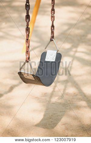 Empty swing on children playground in city.