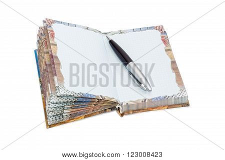 Pen on an open paper notebook of small format with hard cover and sheets of squared paper and decorations on a light background