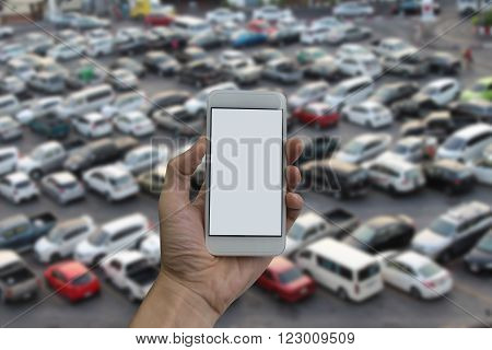 man hand holding empty screen of smart phone and Blurred outdoor parking lot full of cars background.