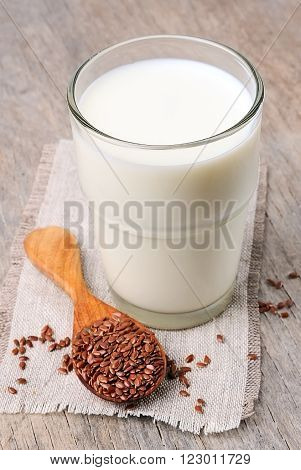 Flax milk and flax seed on a wooden background