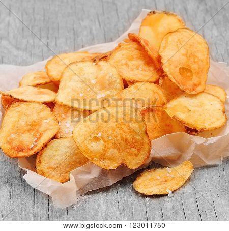 Homemade potato chips closeup on wooden texture