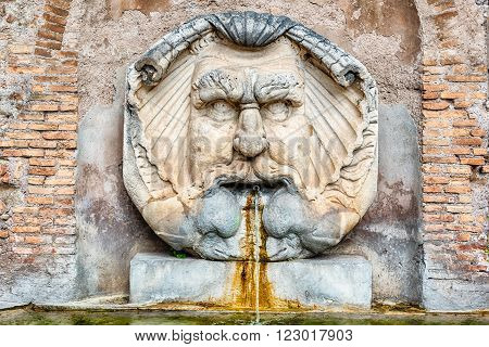 Fountain with large mask in the courtyard of Santa Sabina Basilica in Rome Italy