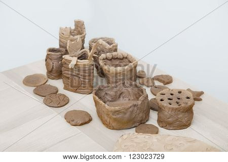 Many amateur handmade unbaked clay moldings on a wooden table
