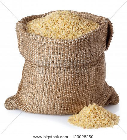 Bulghur or couscous in burlap bag with scattered heap isolated on white background
