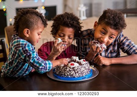 Three afro boys eating cake. Three black kids eat cake. Time for dessert. They waited for so long.