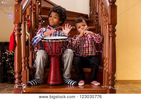 Two afro boys play music. Kids playing music on stairs. Creative duet of young musicians. Starting a music tour.