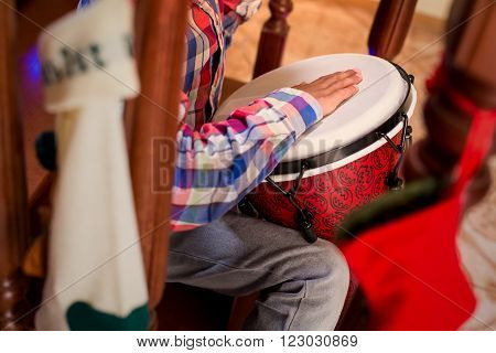 Mulatto child playing percussion drum. Boy plays djembe on stairs. Lively Christmas music at home. Little musician's holidays.