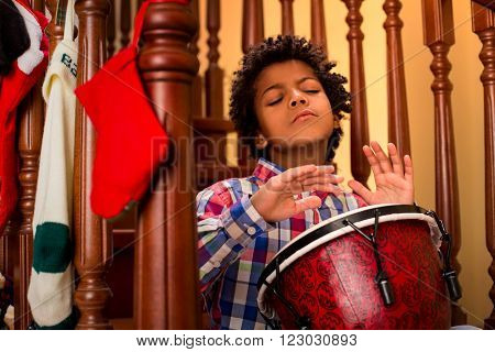 Enthusiastic darkskinned boy playing drum. Kid plays drum on stairs. His inspiration is limitless. Let the music flow.