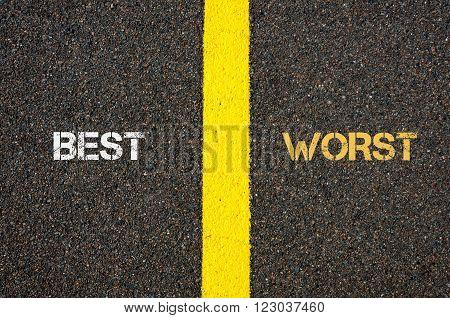 Antonym concept of BEST versus WORST written over tarmac, road marking yellow paint separating line between words