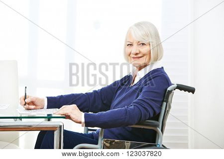 Smiling senior woman in wheelchair on a table doing memory training
