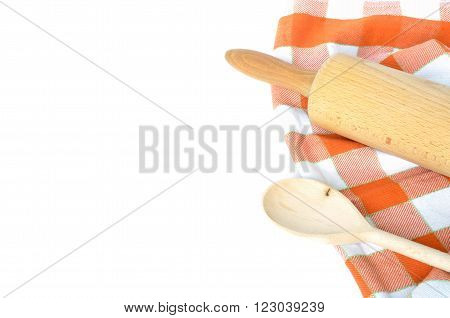 Checkered dishcloth wooden rolling pin and spoon isolated on white