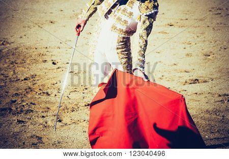 A bullfighter with estoque and muleta giving a pass in the bullring. Corrida de toros