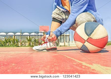 Fit young man hands tying shoes with basketball next him - Healthy guy training on beach sand camp contest - Sport and trends concept - Sunny day in early autumn - Focus on hands shoes