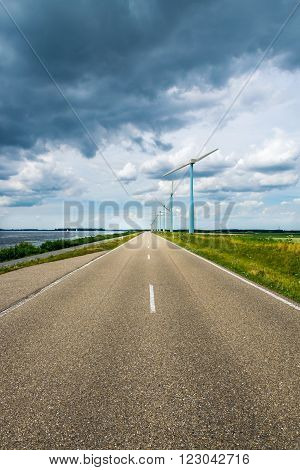 Dutch road with windmills, lake and impressive clouds