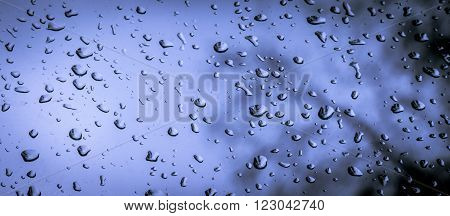 raindrops against a cold and dark sky on a window
