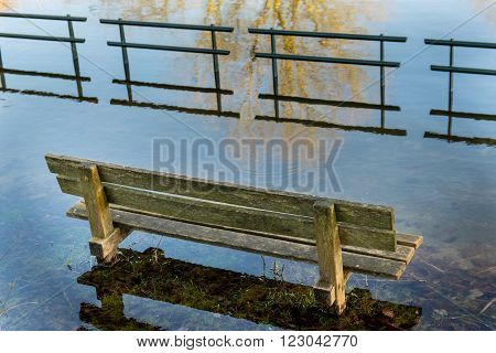 Flooded bench near a pond after heavy rains