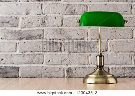Green and gold banker lamp on the desk with old brick wall background
