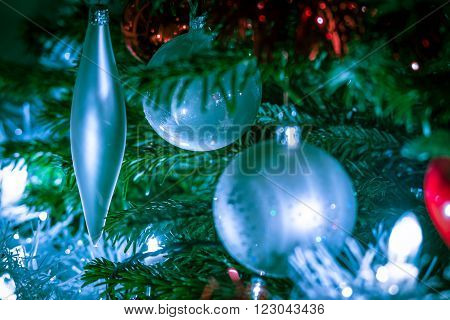 cold christmas balls and decorations hanging in a christmastree