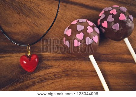 Cakepops and red heart decoration on a wooden background