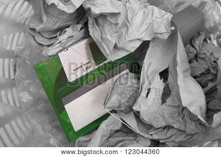 Old green floppy disc in a rubbish bin
