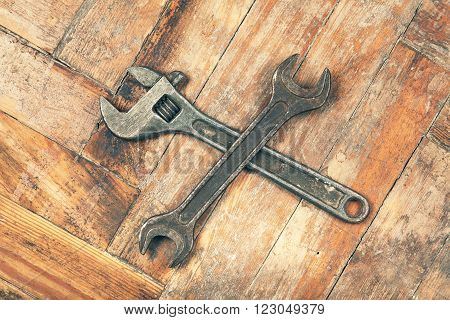 Old crossed adjustable spanner wrench on wooden floor