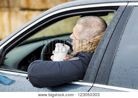 Man drinking soda in the car in winter day