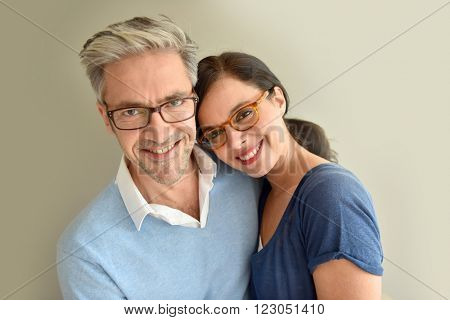 Middle-aged couple with eyeglasses on beige background