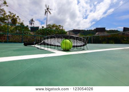 Tennis ball and racket on court close up