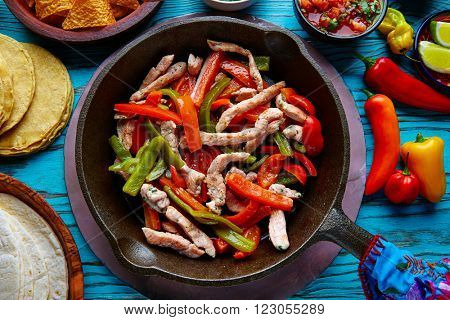 chicken fajitas in a pan with sauces chili and sides Mexican food