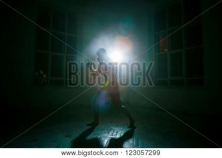 The young male athlete kickboxing on a black background