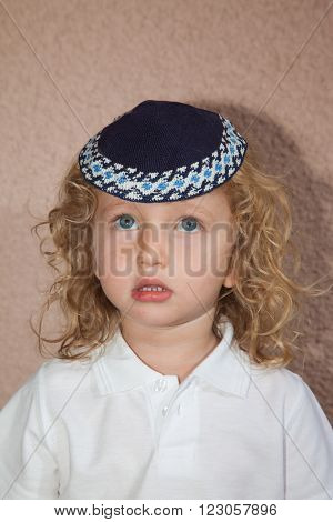 Autumn holiday of Sukkot. The charming little boy with long blond curls and blue eyes in the Jewish knitted kippah