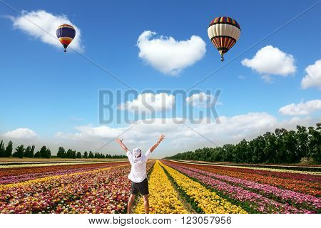 Enthusiastic tourist in white shirt and bandana greets the rising sun. Flower kibbutz near Gaza Strip.  Flowers on the field planted by color stripes