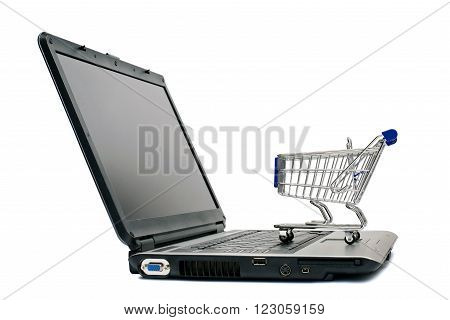 Laptop with shopping cart isolated on white.  Concept of online shopping or e-commerce.