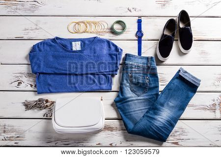 Woman's blue pullover with accessories. Outfit and purse on showcase. Old shelf with new clothes. Lady's simple clothes and accessories.