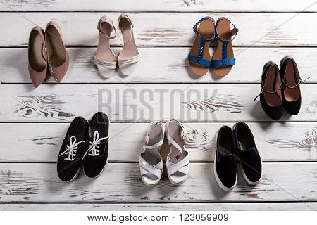 Heel shoes and casual keds. Stylish shoes on woodern floor. Lady's fashinable footwear. Shoes for warm season.