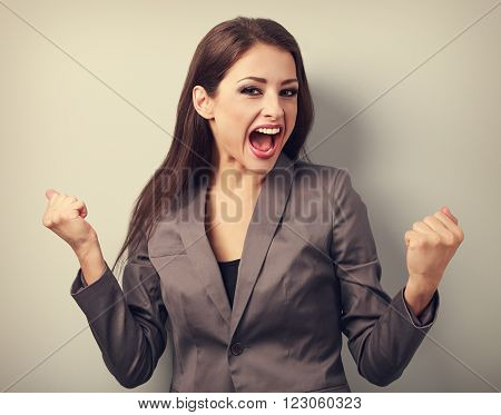 Excited winner business woman with opened mouth. Happy young satisfacted female showing the gesture yes by fists. Vintage portrait