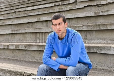 Unhappy Teenage Student Sitting Outside On Stadium Steps