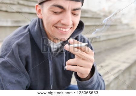 problem of adolescence.Sad and thinker teenager smoking cigarette in urban setting