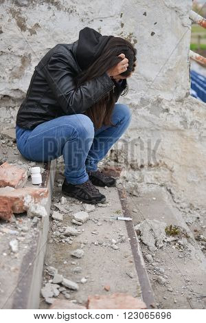 Drug overdose concept - young depressive woman stand on the steps of the old stadium Syringe and pills near her