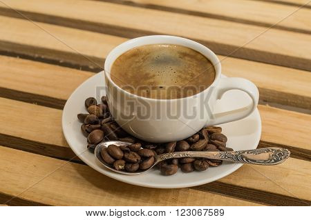 White Cup of black coffee and grain on the dish.