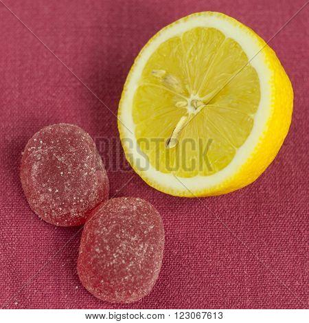 Half a lemon lying near the jelly on the tablecloth.