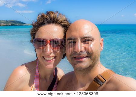 happy couple doing self portrait at the beach