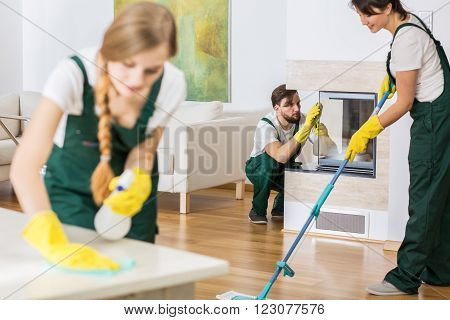Three young professional cleaners in uniforms cleaning spacious living room