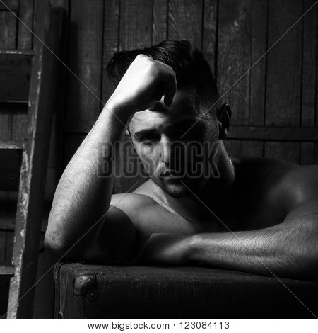Handsome sexy sensual muscular stylish young man topless with bare torso and beautiful body sitting near stairs with hard big retro suit case indoor on wooden background, square picture