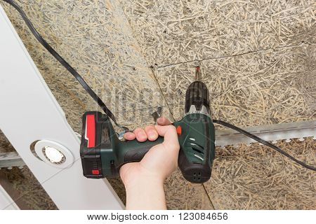 Screwdriver Drives Screws Into Ceiling Of Fiberboard In Hand