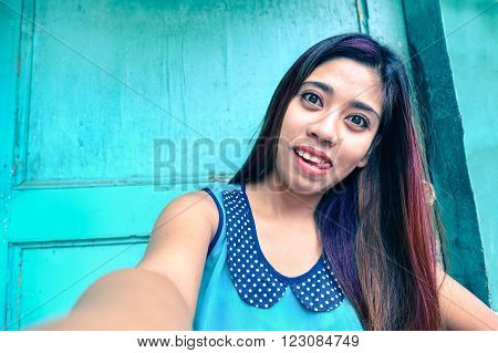 Cheerful asian woman taking selfie with funny face and tongue out - Young filipino girl having fun doing self photo next to blue old wood background - Concept of joyful youth and carefree life